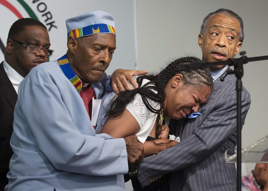 Esaw Garner, center, wife of Eric Garner, breaks down in the arms of Rev. Herbert Daughtry and Rev. Al Sharpton, right, during a rally at the National Action Network headquarters for Eric Garner, Saturday, July 19, 2014, in New York. Garner, 43, died Thursday, during an arrest in Staten Island, when a plain-clothes police officer placed him in what appeared be a chokehold while several others brought him to the ground and struggled to place him in handcuffs. (AP Photo/John Minchillo)