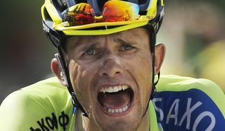 Poland's Rafal Majka crosses the finish line to win the fourteenth stage of the Tour de France cycling race over 177 kilometers (110 miles) with start in Grenoble and finish in Risoul, France, Saturday, July 19, 2014. (AP Photo/Peter Dejong)
