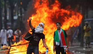A pro-Hamas demonstrator throws a stone toward riot police, during a demonstration in Paris on July 19. (AP Photo/Thibault Camus)