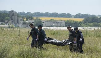 Rescue workers carry a plastic bag with a dead body at the crash site of a Malaysia Airlines jet near the village of Hrabove, eastern Ukraine, Saturday, July 19, 2014. Ukraine accused Russia on Saturday of helping separatist rebels destroy evidence at the crash site of a Malaysia Airlines plane shot down in rebel-held territory — a charge the rebels denied. (AP Photo/Evgeniy Maloletka)