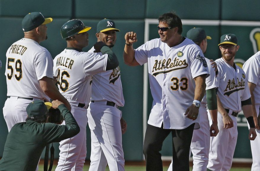 **FILE** Former Oakland Athletic Jose Canseco (33) is welcomed by the team, including first base coach Tye Waller (46) during a pre-game ceremony honoring the reunion of players from the 1989 world championship team prior to the baseball game against the Baltimore Orioles Saturday, July 19, 2014, in Oakland, Calif. (AP Photo/Ben Margot)