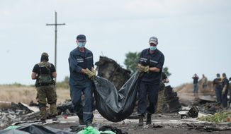 Sorrow: Ukrainian emergency workers carry a victim's body in a bag at the crash site of Malaysia Airlines Flight 17, located near the village of Hrabove. (Associated Press)