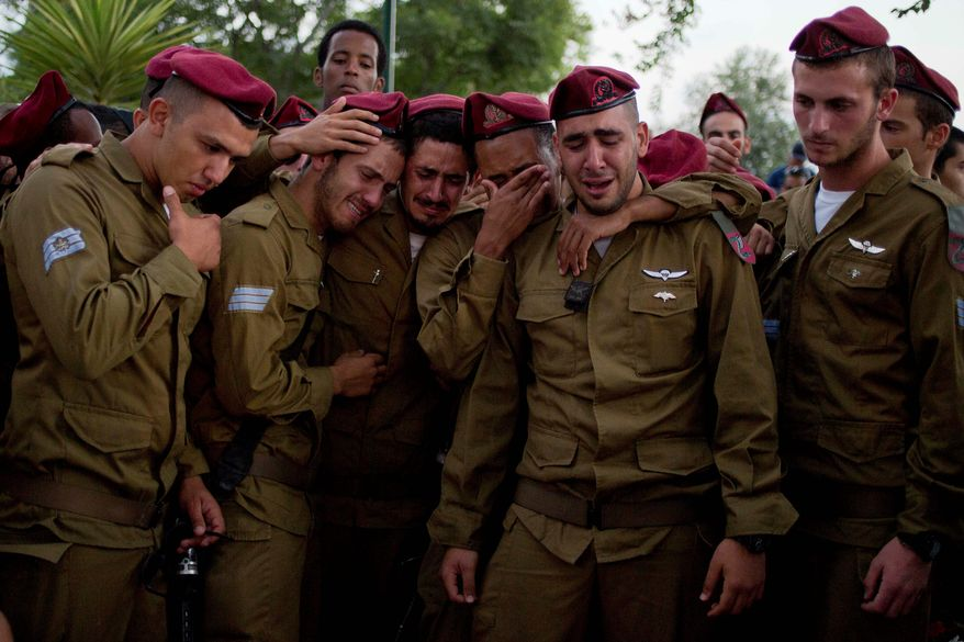 SORROW: Israeli soldiers of the Paratroopers Brigade mourn over the grave of Sgt. Bnaya Rubel during his funeral at the military cemetery in Holon, Israel. He was killed in a clash with Palestinian militants in Gaza on Saturday. (Associated Press)