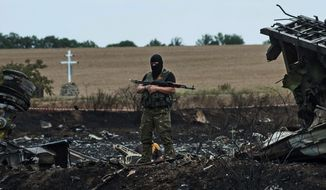 "A pro-Russia fighter guards the crash site of Malaysia Airlines Flight 17 in eastern Ukraine on Sunday. If the Russian Federation is shown to be liable for the deaths of 298 people from various countries, it could lose ""sovereign immunity"" and face complex criminal charges and civil suits. (Associated Press)"