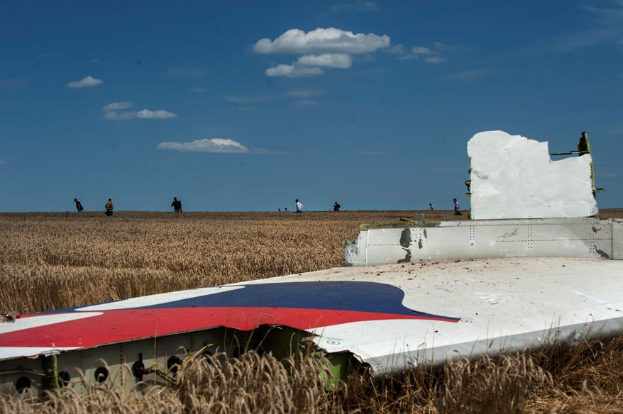 A piece of the crashed jet lies in the grass near the village of Hrabove. U.S. and European leaders demanded that Russian President Vladimir Putin ensure that rebels allow international investigators full access to the shot-down plane's crash site.