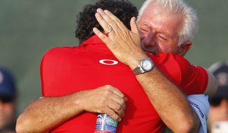 **FILE** Rory McIlroy of Northern Ireland hugs his father Gerry McIlroy after the final round of the PGA Championship golf tournament on the Ocean Course of the Kiawah Island Golf Resort in Kiawah Island, S.C., Sunday, Aug. 12, 2012. (AP Photo/Chuck Burton)