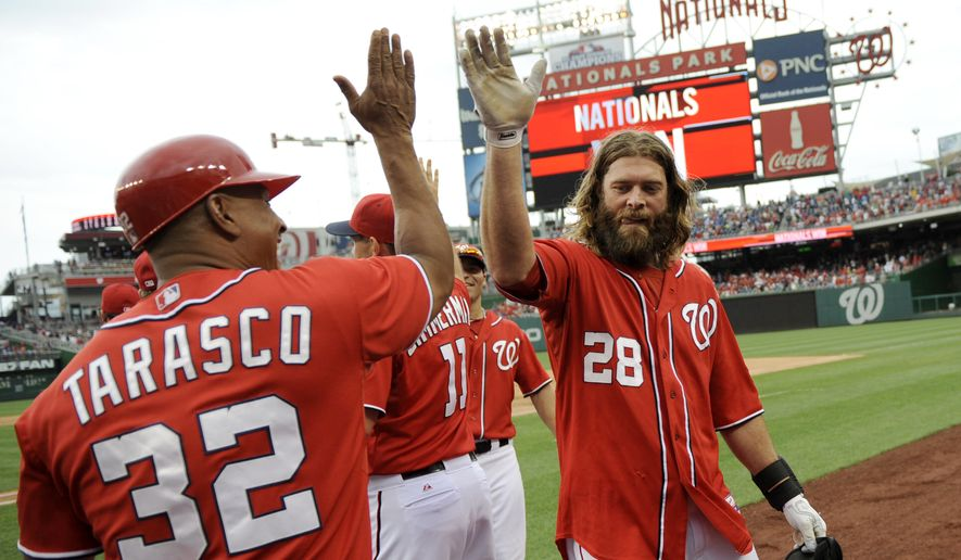 Washington Nationals' Jayson Werth (28) celebrates 5-4 win over the Milwaukee Brewers with first base coach Tony Tarasco (32) after a baseball game, Sunday, July 20, 2014, in Washington. (AP Photo/Nick Wass)
