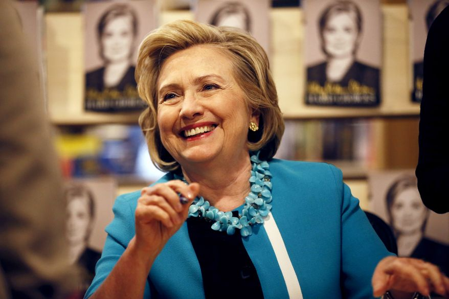 """Hillary Rodham Clinton signs copies of her new book """"Hard Choices"""" at the Common Good Books store, Sunday July 20, 2014 in St Paul, Minn. (AP Photo/The Star Tribune, Jerry Holt)"""