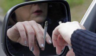 A woman smokes a cigarette. (Associated Press) ** FILE **