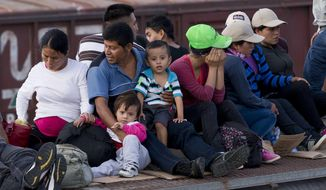 ** FILE ** In this July 12, 2014, photo, Central American migrants ride a freight train during their journey toward the U.S.-Mexico border in Ixtepec, Mexico. The number of family units and unaccompanied children arrested by Border Patrol in the Rio Grande Valley has doubled in the first nine months of this fiscal year compared to the same period last year.  (AP Photo/Eduardo Verdugo)