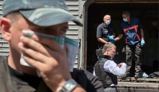 A difficult duty: The stench of death was nearly overwhelming Monday as Alexander Hug (center right), deputy head of the Organization for Security and Cooperation in Europe, led a forensics investigation team near the crash site of Malaysia Airlines Flight 17 in eastern Ukraine. (Associated Press)