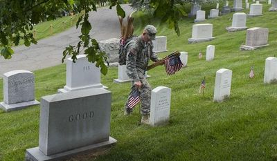 "A soldier of the 3rd U.S. Infantry Regiment, also known as The Old Guard, places flags at grave sites at Arlington National Cemetery in Arlington, Va., Thursday, May 22, 2014, as part of the annual ""Flags-In"" ceremony in preparation for Memorial Day. (AP Photo/Cliff Owen)"