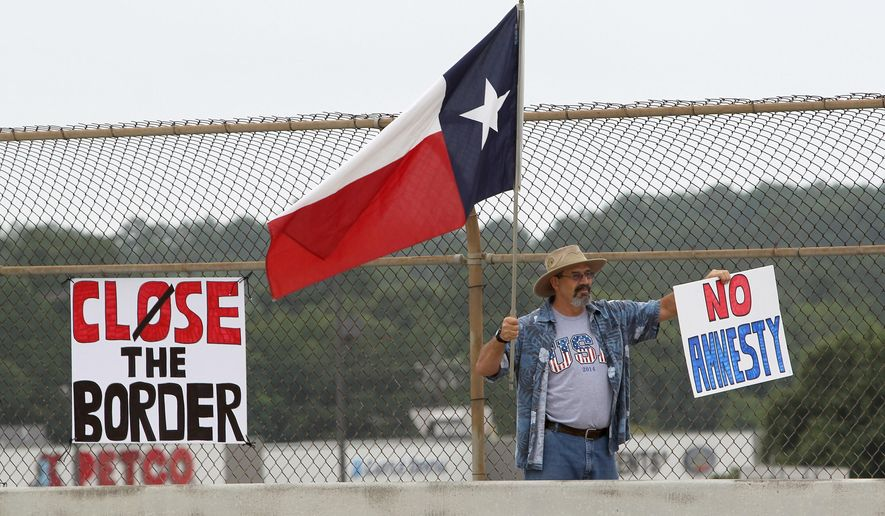 A protester waves a Texas flag and anti-immigration signs during a protest against people who immigrate illegally, Saturday, July 19, 2014, in Conroe, Texas. Texas Gov. Rick Perry took his border security criticisms to an audience of Hispanic ministers in San Antonio, telling them the federal government should put more Border Patrol troops on the ground and drones in the air to secure the Texas-Mexico border. (AP Photo/Conroe Courier, Jason Fochtman)