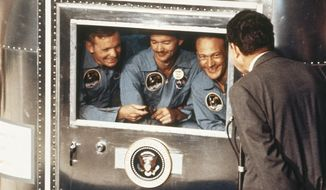 "FILE - In this July 24, 1969 file photo, President  Richard Nixon, right, greets the Apollo 11 astronauts in the quarantine van on board the U.S.S. Hornet after splashdown and recovery. The Apollo 11 crew from left are Neil Armstrong, Michael Collins, and Edwin ""Buzz"" Aldrin. Armstrong and Aldrin became the first men to walk on the moon after blastoff from Cape Kennedy, Fla., on July 16, 1969. (AP Photo, File)"