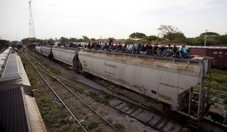 In this July 12, 2014, photo, Central American migrants ride a freight train during their journey toward the U.S.-Mexico border in Ixtepec, Mexico. Many of the children and teenagers who travelled to the United States recently said they did so after hearing they would be allowed to stay. The U.S. generally releases unaccompanied children to parents or relatives while their cases take years to wend through overwhelmed immigration courts. (AP Photo/Eduardo Verdugo)