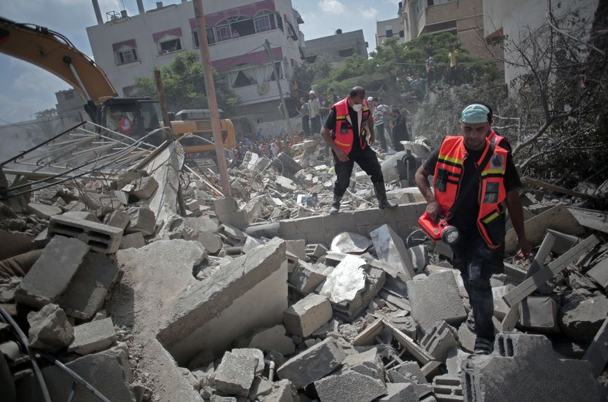 Palestinian rescue workers search for survivors under the rubble of a house was destroyed by an Israeli missile strike, in Gaza City, Monday, July 21, 2014.  On Sunday, the first major ground battle in two weeks of Israel-Hamas fighting exacted a steep price, killing scores of Palestinians and over a dozen Israeli soldiers and forcing thousands of terrified Palestinian civilians to flee their devastated Shijaiyah neighborhood, which Israel says is a major source for rocket fire against its civilians. (AP Photo/Khalil Hamra)