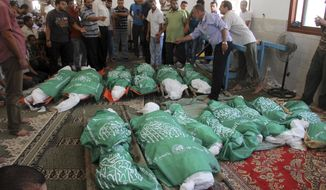 "Palestinians gather around the Hamas green flag-draped bodies of 17 members of the Abu Jamea immediate and extended family, killed by an Israeli strike at their house, during their funeral at the main mosque in Khan Younis, in the southern Gaza Strip, Monday, July 21, 2014. The top Hamas leader in the Gaza Strip signaled Monday that the Islamic militant group will not agree to an unconditional cease-fire with Israel, while Israel's defense minister pledged to keep fighting ""as long as necessary,"" raising new doubt about the highest-level mediation mission in two weeks. (AP Photo/Hatem Ali)"