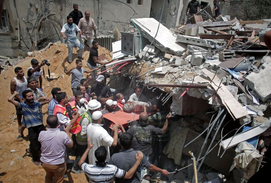 Palestinian rescuers release a lifeless body from the rubble of a house was destroyed by an Israeli missile strike, in Gaza City, Monday, July 21, 2014. On Sunday, the first major ground battle in two weeks of Israel-Hamas fighting exacted a steep price, killing scores of Palestinians and over a dozen Israeli soldiers and forcing thousands of terrified Palestinian civilians to flee their devastated Shijaiyah neighborhood, which Israel says is a major source for rocket fire against its civilians. (AP Photo/Khalil Hamra)