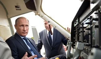 """Russian President Vladimir Putin, left, sits in an aircraft cockpit the Progress State Research and Production Space Centre (also known as TsSKB-Progress) in Samara, Russia, Monday, July 21, 2014. Putin has lambasted those who use the downing of a passenger jet in eastern Ukraine for """"mercenary objectives,"""" the Kremlin said Monday. In a statement posted on the Kremlin website, Putin again lashed out at Ukraine for ongoing violence with pro-Russian rebels in the eastern part of the country. (AP Photo/RIA-Novosti, Alexei Nikolsky, Presidential Press Service)"""