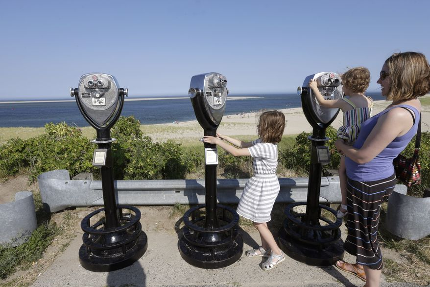 In this July 2, 2014, photo, Molly Saint-James, of Baltimore, right, helps her daughters Ellie McDonald, left, 6, and Poppy McDonald, 3, use telescopic viewers overlooking a beach while on vacation in Chatham, Mass. (AP Photo/Steven Senne)