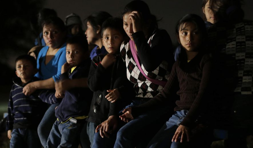 FILE - This June 25, 2014, file photo shows a group of  immigrants from Honduras and El Salvador who crossed the U.S.-Mexico border illegally are stopped in Granjeno, Texas. The influx at the border is largely families with children or by minors traveling alone. (AP Photo/Eric Gay, File)