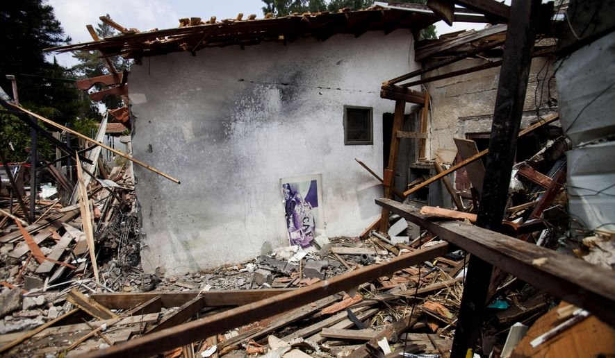 A destroyed house that was hit by a rocket fired by Palestinian militants from Gaza, in Yahud, a Tel Aviv suburb near the airport, central Israel, Tuesday, July 22, 2014. As a result, Delta Air Lines and U.S. Airlines decided to cancel their scheduled flights to Israel.(AP Photo/Dan Balilty)