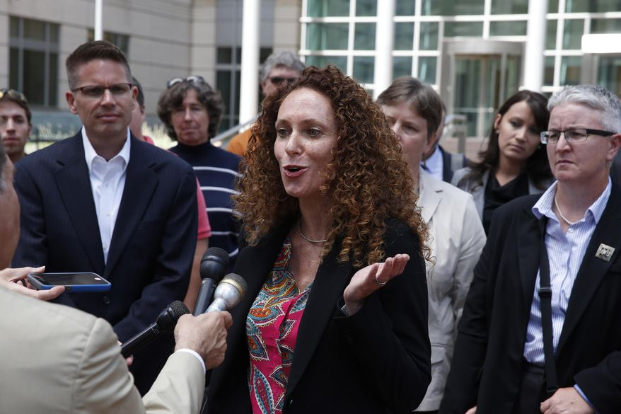 Attorney Mari Newman, center, talks with members of the media, as she stands with her plaintiffs and their supporters following a court hearing on sam sex marriage at the Federal District Court, in Denver, Tuesday, July 22, 2014. (AP Photo/Brennan Linsley)