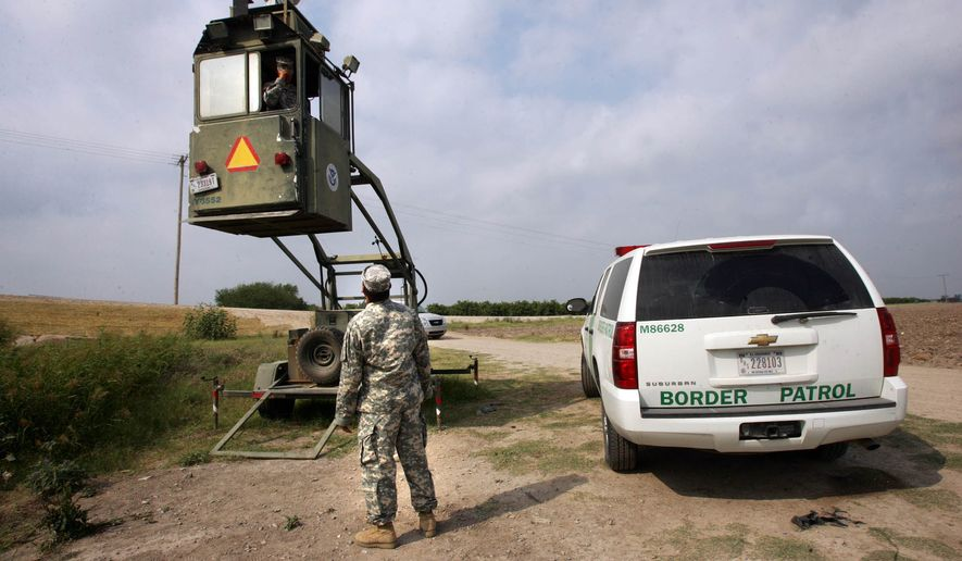 ** FILE ** In this April 19, 2011, file photo, a member of the National Guard checks on his colleague inside a Border Patrol Skybox near the Hidalgo International Bridge in Hidalgo, Texas. (AP Photo/Delcia Lopez, File)