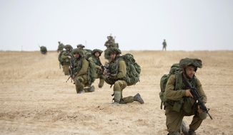 Israeli soldiers kneel during a drill near Israel and Gaza border, Tuesday, July 22, 2014. Israeli airstrikes pummeled a wide range of targets in the Gaza Strip on Tuesday as the U.N. chief and the U.S. secretary of state began an intensive effort to end more than two weeks of fighting that has killed hundreds of Palestinians and dozens of Israelis.(AP Photo/Tsafrir Abayov)