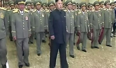 In this Tuesday, July 8, 2014 image made from video, North Korean leader Kim Jong Un, center, visits Kumsusan Palace of the Sun to mark the 20th anniversary of the death of its first leader, Kim Il Sung, in Pyongyang, North Korea. Kim seemed to have somehow hurt his leg enough to require a slight, but visible, limp as he marched across the stage Tuesday to assume his position of honor. He limped again as he left the room when the event was over. (AP Photo/KRT via AP Video) TV OUT, NORTH KOREA OUT