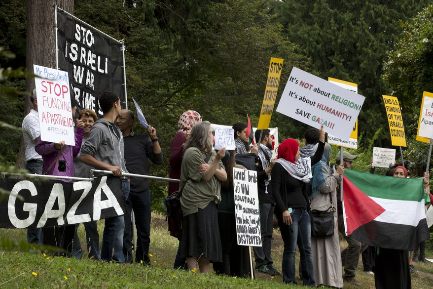 Pro-Palestinian protesters chant near a private residence where President Barack Obama had arrived to attend a fundraiser in Seattle Tuesday, July 22, 2014, the start of a three-day West Coast trip that is planned to include at least five fundraising events in Seattle, San Francisco and Los Angeles. (AP Photo)