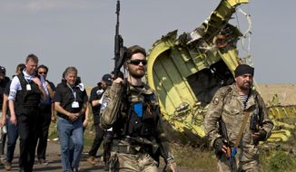 ** FILE ** Pro-Russian rebels, right, followed by members of the OSCE mission, walk by plane wreckage as they arrive for a media briefing at the crash site of Malaysia Airlines Flight 17, near the village of Hrabove, eastern Ukraine, Tuesday, July 22, 2014. A team of Malaysian investigators visited the site along with members of the OSCE mission for the first time since last week's crash. (AP Photo/Vadim Ghirda)