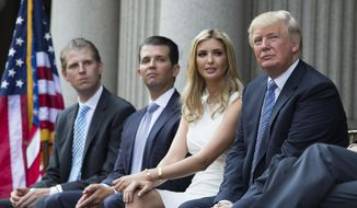 Donald Trump, right, sits with, from left, Eric Trump, Donald Trump Jr. and Ivanka Trump during a ground breaking ceremony for the Trump International Hotel on the site of the Old Post Office, on Wednesday, July 23, 2014, in Washington. (AP Photo) ** FILE **