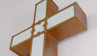 This photo taken on July 19, 2014, shows a cross hanging at the altar of the Conesville Methodist Church in Conesville, Iowa. After 113 years, the church is closing and some expect the historic structure in eastern Iowa will eventually be demolished.  Lay Leader Terri Fitchner told the Muscatine Journal the closure reflects an aging congregation and no new members, and a troublesome bat infestation. (AP Photo/The Muscatine Journal, Ky Cochran)
