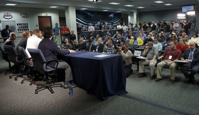 St. Louis Rams seventh-round draft pick Michael Sam, seated at table in white shirt, speaks during a news conference along with Rams coach Jeff Fisher, right foreground general manager Les Snead; and chief operating officer Kevin Demoff, left, at the NFL football team's practice facility Tuesday, May 13, 2014, in St. Louis. (AP Photo/Jeff Roberson)