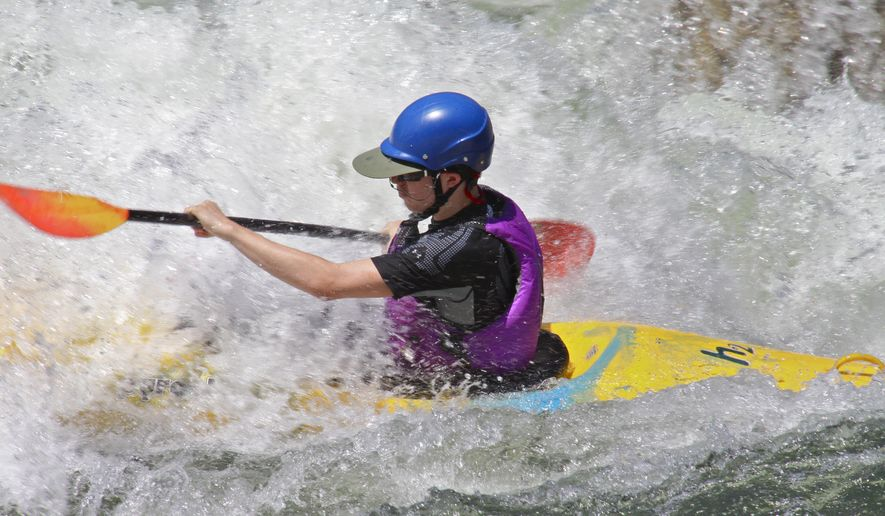Whitewater boils all around a kayaker on the Main Payette, July 3, 2014. (AP Photo/Idaho Statesman, Pete Zimowsky)