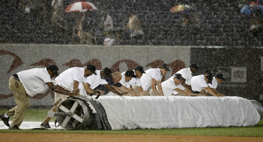 Grounds crew members unroll the tarp during a sudden rainstorm in the fifth inning of a baseball game between the Texas Rangers and the New York Yankees at Yankee Stadium in New York, Wednesday, July 23, 2014.  (AP Photo)