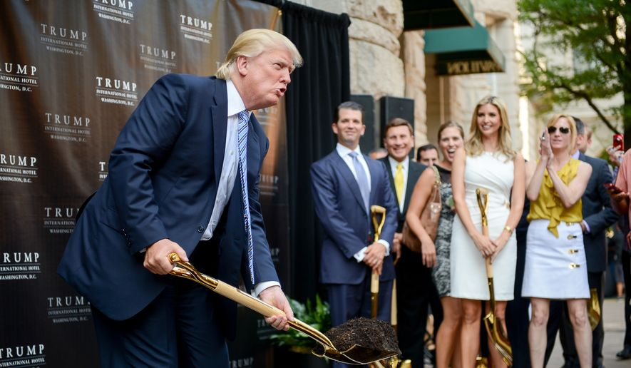 Ivanka Trump, second from right, watches as her father Donald J. Trump, left, poses for photos during a groundbreaking ceremony for the Trump International Hotel, a $200 million redevelopment of the iconic Old Post Office building on Pennsylvania Ave., Washington, D.C., Wednesday, July 23, 2014. (Andrew Harnik/The Washington Times)
