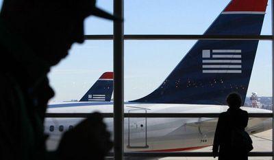 **FILE** Passengers walk past US Airways planes at Ronald Reagan Washington National Airport in suburban Washington on Dec. 27, 2009. (Associated Press)