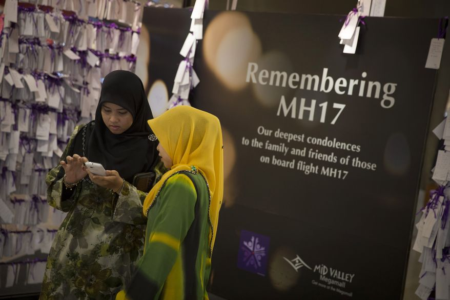 Shoppers take a photo next to prayer notes for passengers aboard Malaysia Airlines Flight 17 at a shopping mall in Kuala Lumpur, Malaysia, Thursday, July 24, 2014. The crash of the Malaysian passenger plane over eastern Ukraine a week ago killed all 298 people. (AP Photo/Vincent Thian)