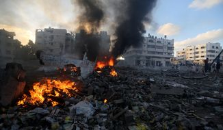 Flames spread over debris after an Israeli airstrike as rescuers inspect the damaged area in Gaza City in the Gaza Strip on Thursday, July 24, 2014. Israeli tanks and warplanes bombarded the Gaza Strip on Thursday, as Hamas militants stuck to their demand for the lifting of an Israeli and Egyptian blockade in the face of U.S. efforts to reach a cease-fire. (AP Photo/Hatem Moussa)