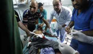 Palestinian medics treat a child wounded in an Israeli strike on a compound housing a U.N. school in Beit Hanoun, in the northern Gaza Strip, at the emergency room of the Kamal Adwan hospital in Beit Lahiya, Thursday, July 24, 2014. Israeli tank shells hit the compound, killing more than a dozen people and wounding dozens more who were seeking shelter from fierce clashes on the streets outside. (AP Photo/Lefteris Pitarakis)