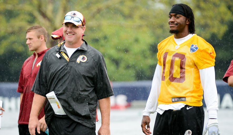 Washington Redskins head coach Jay Gruden, left, chats with Washington Redskins quarterback Robert Griffin III (10) on the opening day of Washington Redskins Training Camp at Bon Secours Training Center, Richmond, Va., Thursday, July 24, 2014. (Andrew Harnik/The Washington Times)