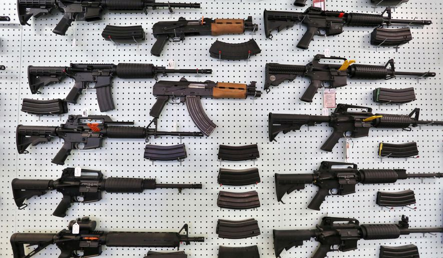 In this July 20, 2014 photo, guns are displayed for sale at Dragonman's, an arms seller east of Colorado Springs, Colo. When Colorado lawmakers expanded background checks on firearms last year, they were expecting a huge increase. But the actual number the first 12 months of the law is far lower than projected, according to an analysis of state data by The Associated Press. (AP Photo/Brennan Linsley)