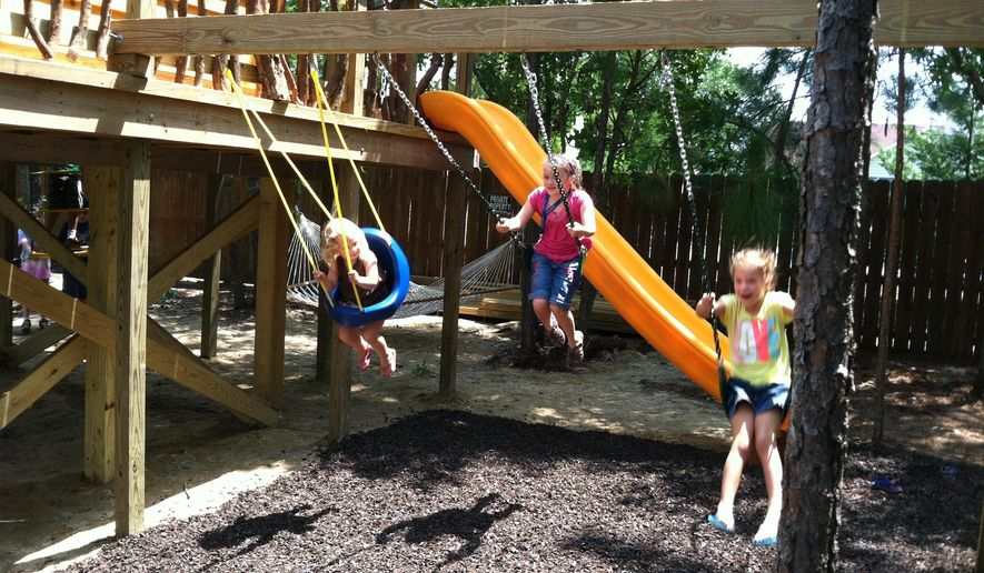ADVANCE FOR SATURDAY, JULY 26 - Evie Wentz, 10, middle, enjoys her new swing set with her friends Annabelle, 6, right, and Lila Baker, 2, on July 12, 2014, in Whispering Pines, N.C. (AP Photo/The Sanford Herald, Zach Potter)