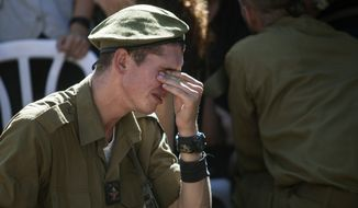 An Israeli soldier mourns over the grave of reserve Master Sgt. Yair Ashkenazy, 36, during his funeral at the military cemetery in Rehovot, Israel, Friday, July 25, 2014. Ashkenazy was killed early Friday during operations in the northern Gaza Strip, the Israel Defense Forces reported. (AP Photo/Dan Balilty)