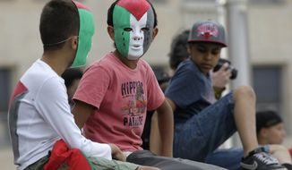 Two boys wearing a mask with the colors of the Palestinian flag, attend a pro-Palestine march in Brussels, Friday, July 25, 2014. Demonstrators marched to show their support for Palestine during the current clashes in Gaza. (AP Photo/Yves Logghe)
