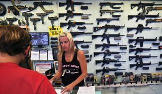 ** FILE ** In this July 20, 2014, photo, with guns displayed for sale behind her, a gun store employee helps a customer at Dragonman's, east of Colorado Springs, Colo. (AP Photo/Brennan Linsley)