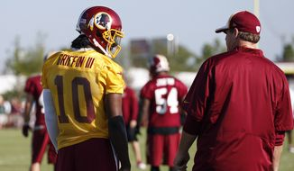 Washington Redskins quarterback Robert Griffin III talks with head coach Jay Gruden during practice at the team's NFL football training facility, Friday, July 25, 2014 in Richmond, Va. (AP Photo)