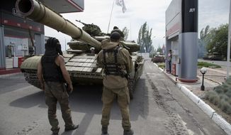 In this photo taken on Thursday, July  17, 2014, Donetsk People's Republic fighters fill their tank with fuel at a gas station in Snizhne, 100 kilometers (62 miles) east of Donetsk, eastern Ukraine. (AP Photo/Dmitry Lovetsky)